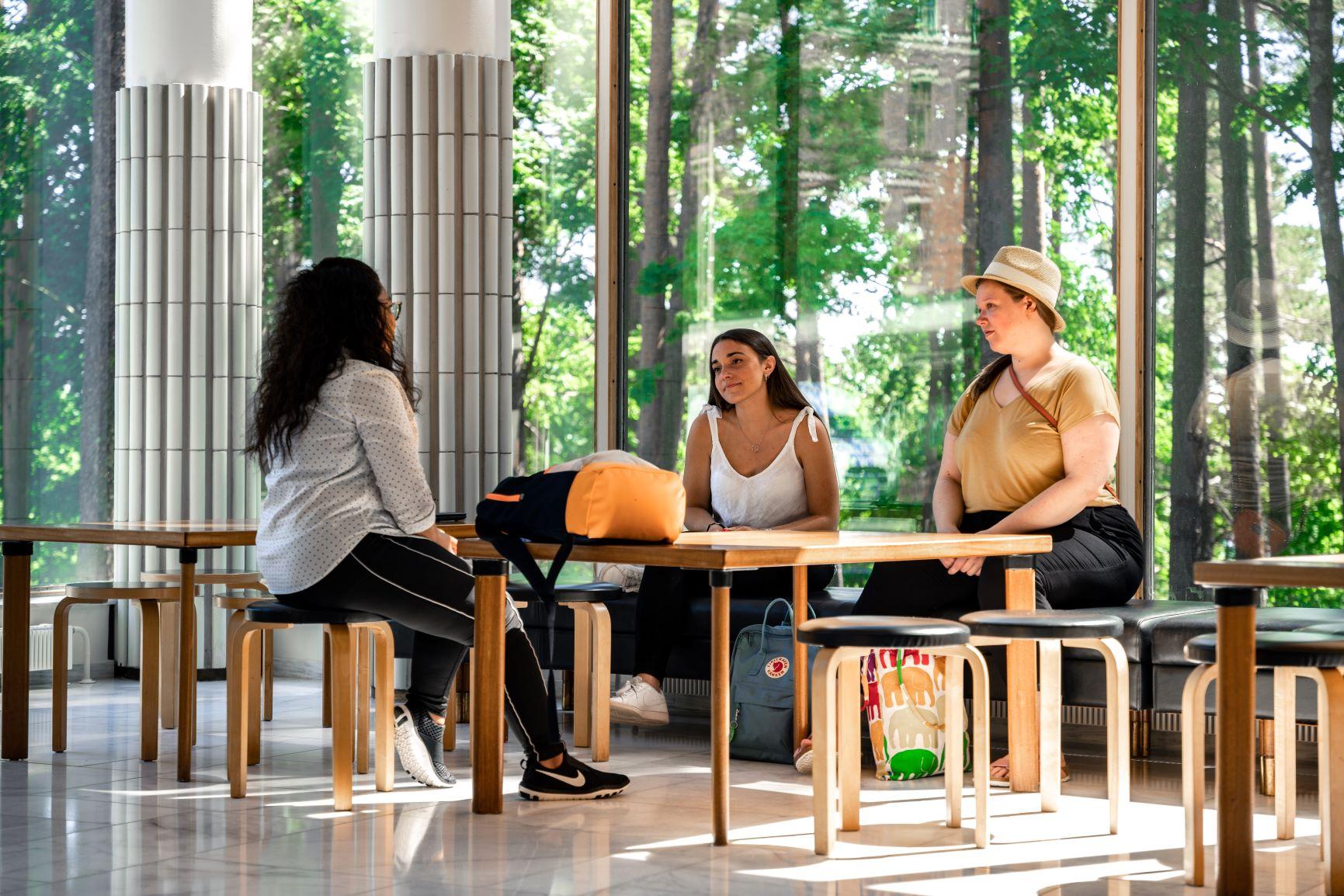 Kolme naisoletettua opiskelijaa istuu kampusrakennuksen aulassa pöydän ympärillä keskustelemassa