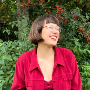 Naishenkilö, iloinen ja naurava ilme, punaiset vaatteet vihreää luontotaustaa vasten